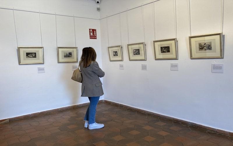 """Vecina de la localidad disfrutando de la serie de grabados """"Los proverbios"""" de Goya"""